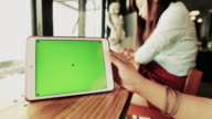 Businesswoman using digital tablet at coffee shop,Green screen video