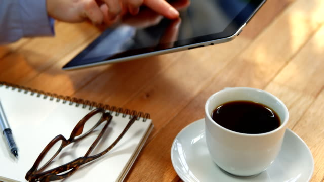 Businesswoman using digital tablet at desk with cup of coffee, spectacles and notebook on table video