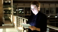 Businesswoman using digital tablet in dark office video