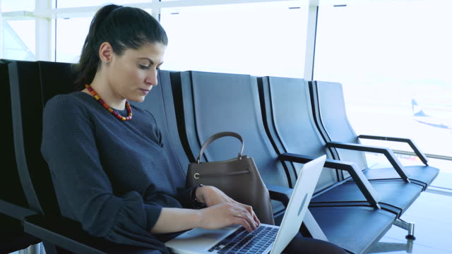 Businesswoman using laptop in airport. video