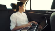 Businesswoman using laptop in the car. video