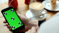 Businesswoman using mobile cell phone with green touch screen in cafe video