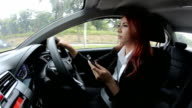 businesswoman using mobile phone while driving video
