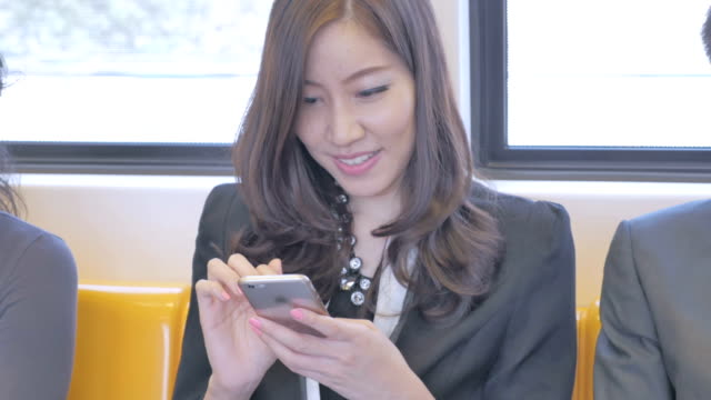 Businesswoman using smartphone on train,Close-up video