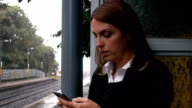 Businesswoman waiting for a train on the phone video