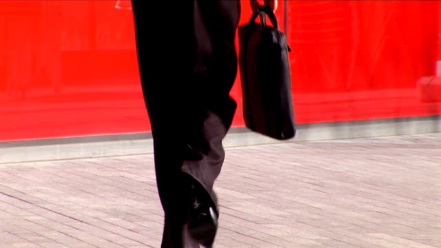 Businesswoman walking with laptop case video