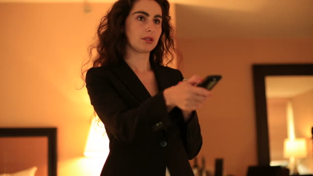 Businesswoman watching TV while on the phone video