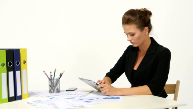 Businesswoman wearing casual shirt sitting at desk and looking latest video