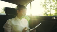 Businesswoman working on a digital tablet in the car. video