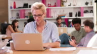 Businesswoman Working On Laptop In Busy Office video