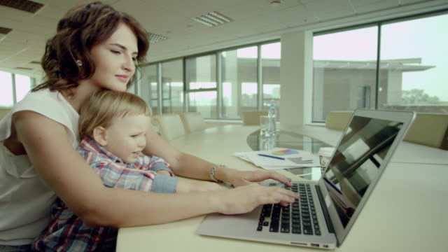 businesswoman working on laptop with baby video