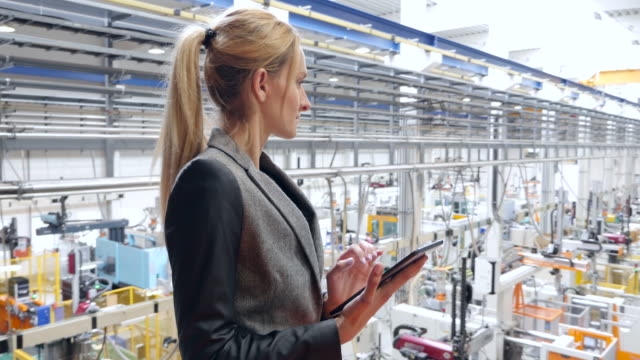 Businesswoman working on tablet in futuristic factory video