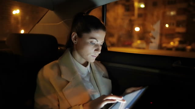 Businesswoman working on the tablet in the car. video