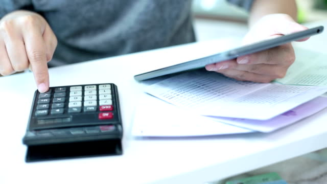 Businesswoman working with calculator in home office video