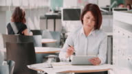 Businesswoman working with digital tablet in an office video