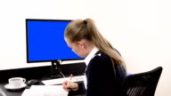 Businesswoman writing notes in office video