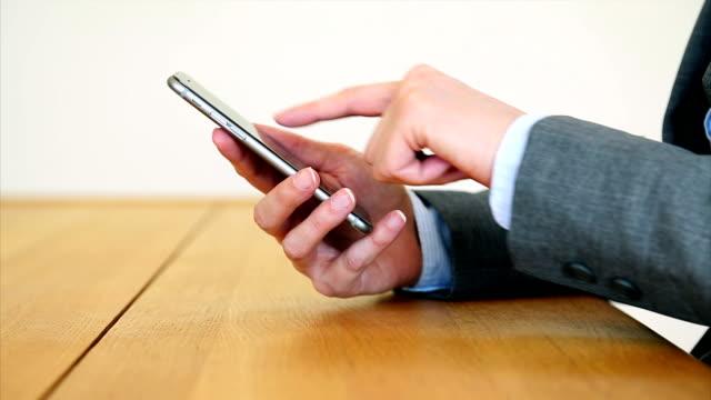Businesswoman's hands using smart phone at desk video