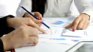 businesswomen meeting: financial analysis with printed financial charts video
