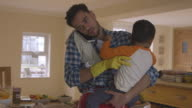 Busy Father Looking After Son Whilst Doing Household Chores video