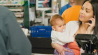 Busy mom at checkout counter video