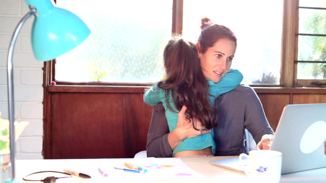 Busy mother at home office desk while daughter hugs her video