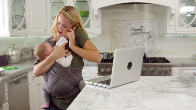 Busy Mother With Baby In Sling At Home Shot On R3D video