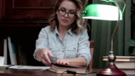 Busy student in glasses working on her report at the desk with a green lamp, going through books and drinking coffee video
