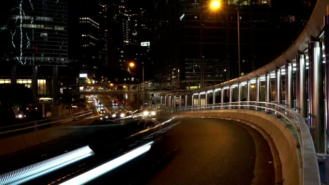 Busy traffic on multiple lane highway and buildings in hong kong at night,time lapse. video