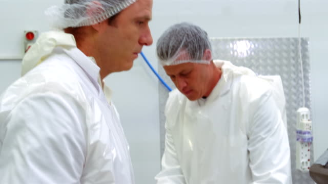Butchers checking the weight of meat at meat factory video