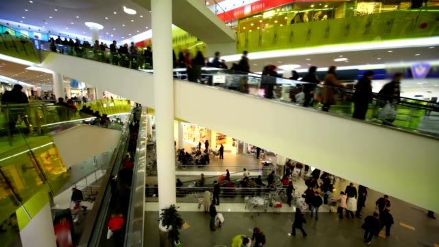 Buyers crowd rushing on escalators in big multistorey mall shop video
