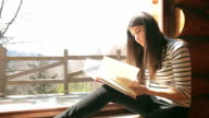 Cabin Retreat - Video of a young woman reading a book by the window. video