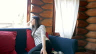 Cabin Retreat - Woman relaxing on the sofa in the cabin. video