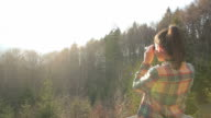 Cabin Retreat - Young woman looking at view with a binocular. video