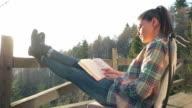 Cabin Retreat - Young woman reading a book. video