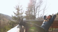 Cabin Retreat - Young woman sitting on the terrace of the cabin and enjoying life. video