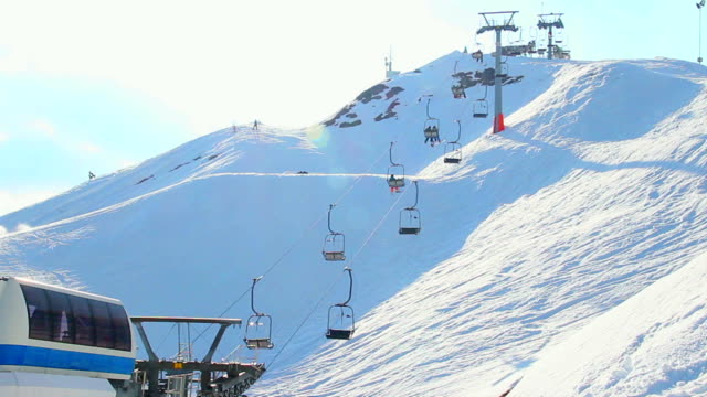 Cable way moving tourists, skiers up down snowy mountain video
