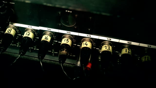 XLR Cables plugged into the back of a mixing console desk, nuMBer-coded. video