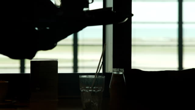Cafe at the airport, waitress putting  glass and coffee cups on table, service video