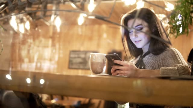 Cafe city lifestyle woman on phone drinking coffee and texting on smartphone app sitting indoor in trendy urban cafe. video