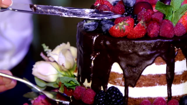 cake with berries and chocolate close up where the couple at the wedding video