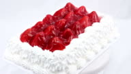 Cake with white frosting and whole strawberry gelatin topping. video