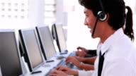 Call centre agents working and talking on headsets video