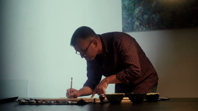 Calligrapher at work. A man holds a calligraphy pen. The art of calligraphy video