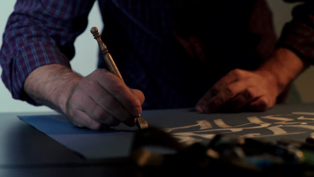 Calligrapher s hands. Calligrapher writes a pen. White ink video