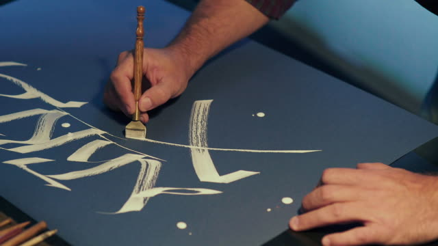 Calligrapher writes a pen. White ink. The art of calligraphy video