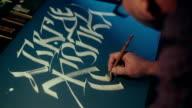 Calligrapher writes canvas pen. Slavic alphabet. White ink on black paper video