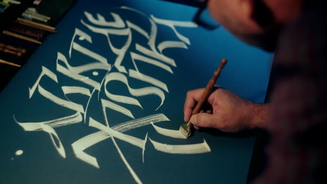 Calligrapher writes canvas pen. Slavic alphabet. White ink on black paper video