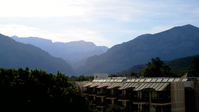 calm landscape with mountains and houses in a forest, no wind, soft sunshine, cloudy sky, summer day video