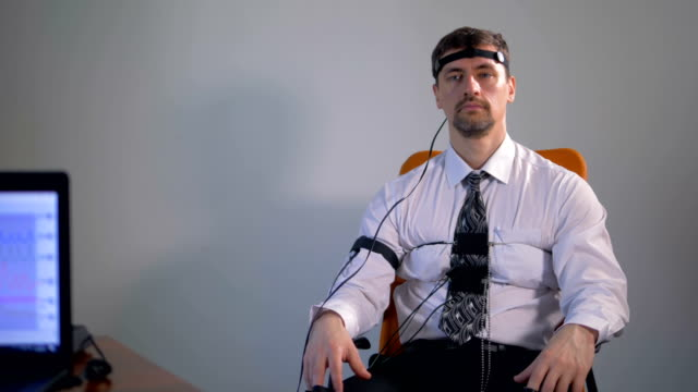 A calm man with polygraph straps attached looking into nothing. video