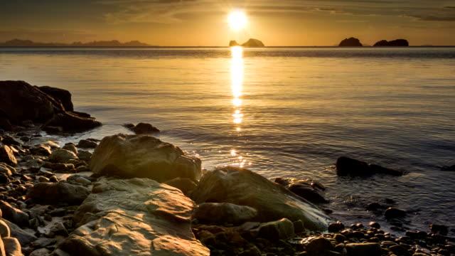 Calm sea at sunset rocks beach video